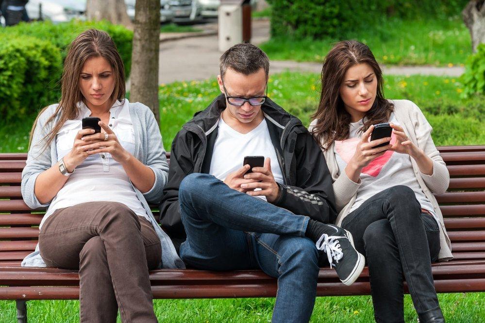 молодые люди с телефонами сидят